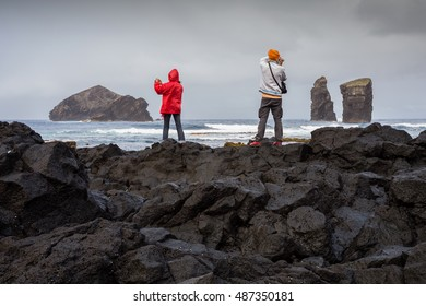 Couple of tourists photographing the Mosteiros Volcanic Beach, Sao Miguel, Azores, Portugal