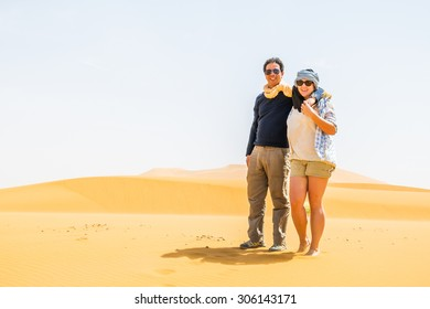 Couple of tourists posing on sand dunes in Merzouga, Morocco