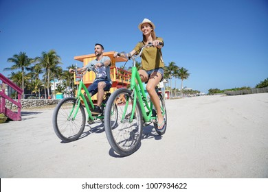 Couple of tourists riding bike in Miami beach