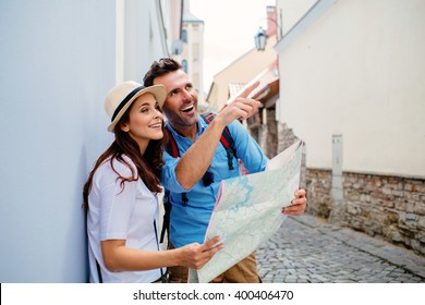 Couple of tourists sightseeing old european  town with map