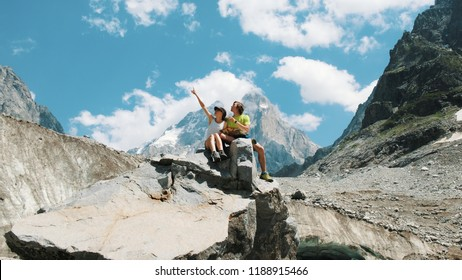 Couple of tourists sit on a rock and study a map, plan a route in a mountain hike.