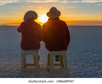 A couple of tourists sitting on benches and enjoying a magnificent sunset in the Uyuni salt flat desert with lens flare, Andes mountain range altiplano, Bolivia, South America.