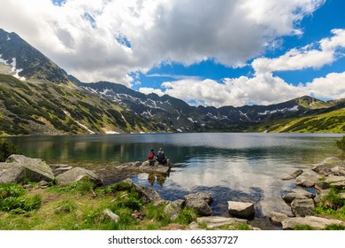 Couple of tourists sitting on a rock in the Valley of five ponds in the Polish Tatras