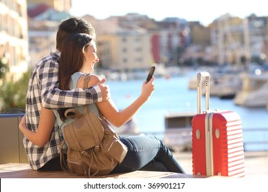 Couple of tourists sitting searching information or booking an hotel on a smart phone on vacations in a colorful port promenade