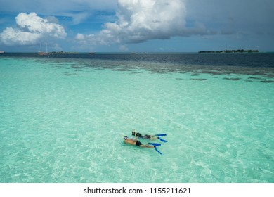 Couple of tourists snorkel in crystal sea in Maldives