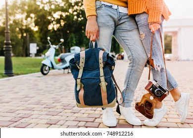 Couple of tourists standing on city square with camera and backpack. Charming female photographer in white shoes posing near boyfriend which holding navy bag.