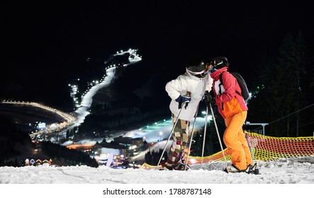 Couple of tourists standing on the hill kissing against amazing night background of illuminated ski pistes, copy space. Concept of active lifestyle, night skiing and relationships.