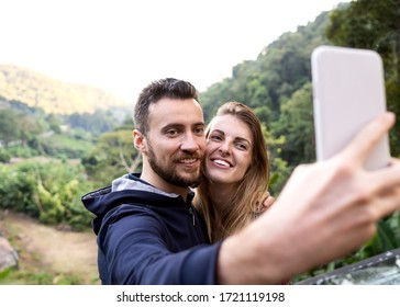 couple of tourists take selfie at sunset in the mountains of Thailand