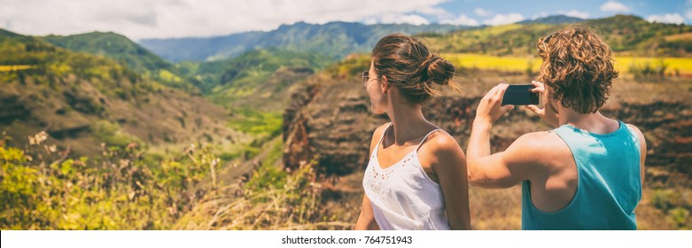 Couple tourists taking phone pictures of Hawaii nature landscape with smartphone camera app. Travel lifestyle people enjoying summer vacation.