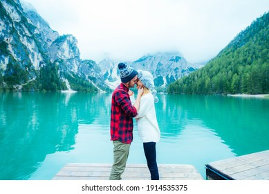 Couple of tourists visiting an alpine lake in Braies, Italy. Boyfriend and girlfriend kissing over a pier on a wanderlust background - Blue vintage filter.