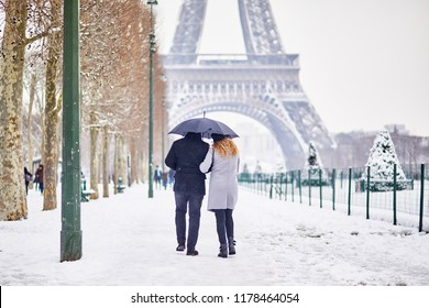 Couple of tourists walking in Paris under umbrella on a day with heavy snow. Unusual weather conditions in Paris