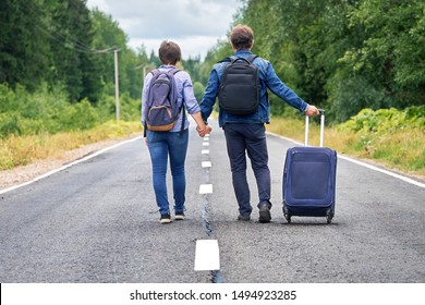 Couple tourists wearing backpacks with a travel bag on wheels walks along the narrow rural road into the distance. Travel and love concept