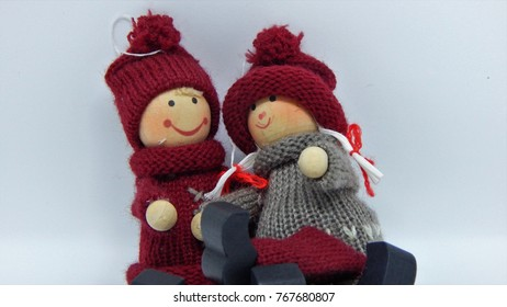 A couple of toys, girl and boy in winter suits, girl sits on boy's knees, cute romance
