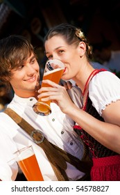 Couple in traditional Bavarian Tracht - Dirndl and Lederhosen - in a beer tent at the Oktoberfest or in a beer garden enjoying a glass of tasty wheat beer