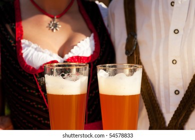 Couple in traditional Bavarian Tracht - Dirndl and Lederhosen - in a beer tent at the Oktoberfest or in a beer garden enjoying a glass of tasty wheat beer, only glasses and torsos to be seen