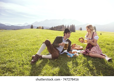 Couple in traditional clothes from Germany drinking beer and eating pretzel in beautiful landscape from Allgau, Bavaria. Couple in bavarian clothes with pretzel and beer in hand