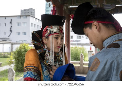 Couple in traditional Mongolian outfits, man is assisting the lady to fix the decorations on her dress