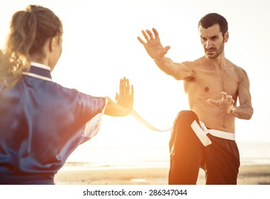 couple training martial arts on the beach. concept about sport and people
