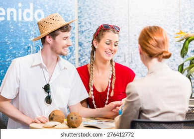 Couple in travel agency booking vacation trip