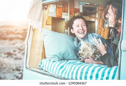 Couple of travel bloggers inside a vintage minivan with their dog - Digital nomads having fun around the world - Love, van lifestyle, alternative job and relationship concept - Focus on man face