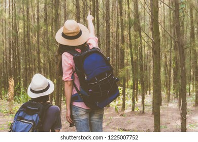 Couple traveler in forest pointing to them traget and exciting with adventure on holiday.
