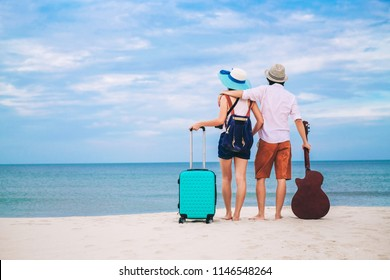 couple of traveler have a baggage and guitar standing on the beach.Asia tourist enjoying at the sea on vacation.