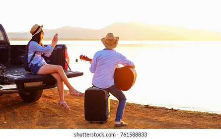 couple traveler have baggage and guitar sitting on hatchback of car and looking for view of lake mountain and sunset near the dam on vacation.silhouette romance concept.