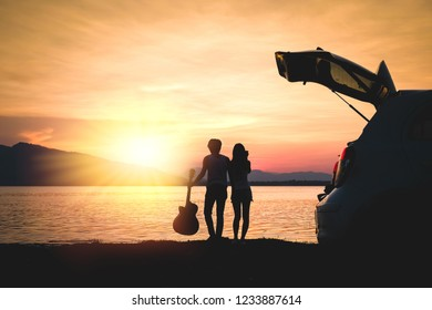 couple traveler have camera and guitar sitting on hatchback of car and looking for view of lake mountain and sunset near the dam on vacation.silhouette romance concept.