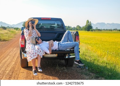 couple traveler have a relax time during traveling beside the road.Asia tourists enjoying for view of nature on hatchback of car on holiday.