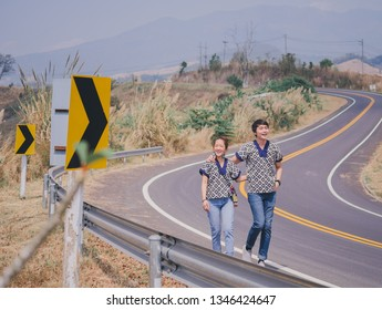 couple traveler in lanna shirt uniform north Thailand walking on the road on mountain with sun light