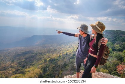 couple traveler are on top of the mountain and taking photo view of nature on holiday.