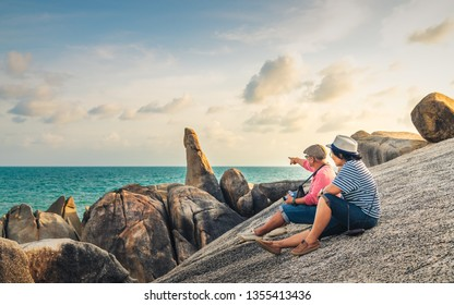 Couple traveler relaxing on rock beach joy fun amazed nature scenic landscape of Hin Ta Hin Yai, Famous landmark tourist travel Samui Thailand summer holiday vacation, Tourism destination place Asia
