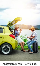 Couple of traveler sitting on hatchback car and play guitar.tourist have a romance time on vacation.