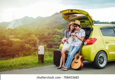 Couple of traveler sitting on hatchback of car and looking at the picture on camera near the road during holiday.Young couple tourist enjoying on vacation.