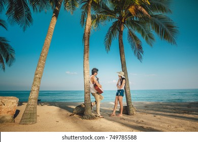 couple traveler standing and playing a guitar under the coconut tree at the beach.Asia tourist have romance time on vacation.