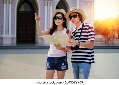 Couple of traveler using local map together for go to destination in the city. tourist couple have a good time on vacation background is the church. Happy family go to travel on holiday.