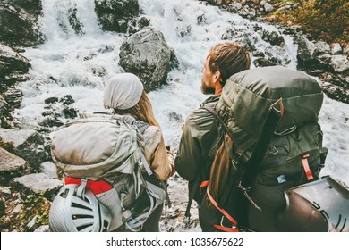 Couple travelers with backpacks into the wild mountains adventure travel outdoor journey in wild together healthy Lifestyle wanderlust concept summer active vacations