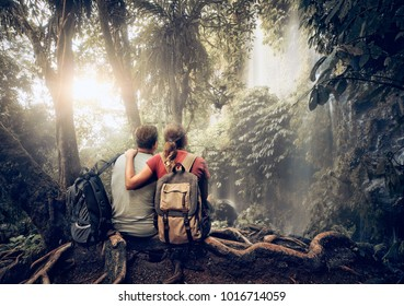 Couple travelers with backpacks relaxing in greens jungle and enjoying view in waterfall. Island Lombok, Indonesia.