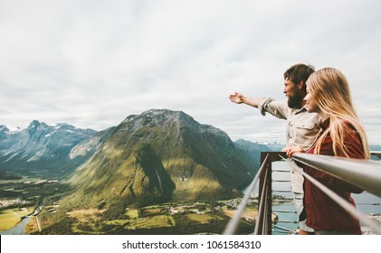 Couple travelers enjoying mountains landscape love and Travel happy emotions Lifestyle adventure vacations concept traveling together in Norway Rampestreken viewpoint