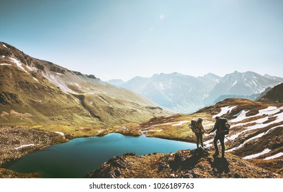 Couple travelers holding hands on mountain cliff over lake together love and Travel Lifestyle wanderlust concept adventure vacations outdoor aerial view