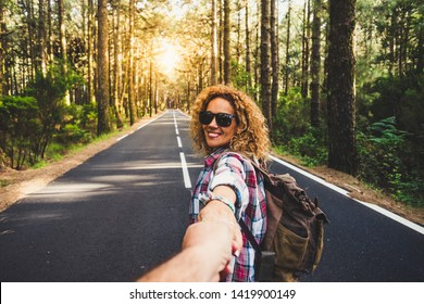 Couple travelers Man and Woman follow holding hands at long way road forest landscape and sun on background Love and Travel happy emotions Lifestyle concept People traveling active adventure vacations