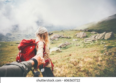 Couple travelers Man and Woman follow holding hands at foggy mountains landscape on background Love and Travel happy emotions Lifestyle concept. Young family traveling active adventure vacations