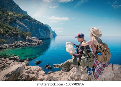 Couple Travelers Man and Woman with a map sitting relax in a hike. Hikers with backpacks in the mountains by the sea. Young family traveling active adventure.