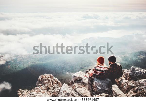 Paare Reisende Mann und Frau sitzen auf Klippen entspannende Berge und Wolken Luftsicht Love und Reisen glückliche Emotionen Lifestyle Konzept. Junge Familienreisende aktive Abenteuerferien
