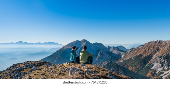 Couple of travelers sitting on cliff relaxing Alps mountains and clouds aerial view, showing direction. Love and Travel happy emotions. Young family traveling active adventure vacations