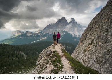 Couple of travelers standing on steep ridge, when dark clouds are passing by the slopes of the mountains