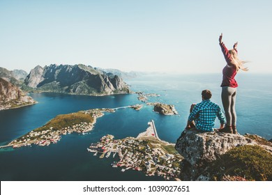 Couple travelers traveling together on top cliff Reinebringen mountain in Norway man and woman family lifestyle concept summer vacations outdoor aerial view Lofoten islands