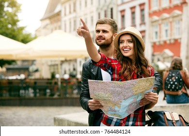 Couple Of Travelers Using Map For Sightseeing In Town. Portrait Of Young Smiling Tourist Man And Woman Holding Map In Hands, Walking On Street And Traveling Together. High Resolution.