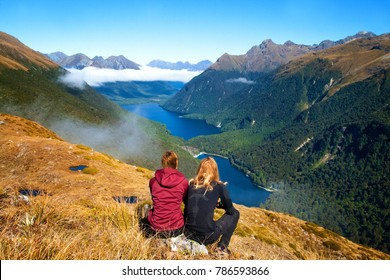 A couple of travelers in wild nature sitting in front of the view of a valley with mountains and clear blue lake. Side trip from Key Summit at Routeburn Track in Fiordland National Park New Zealand