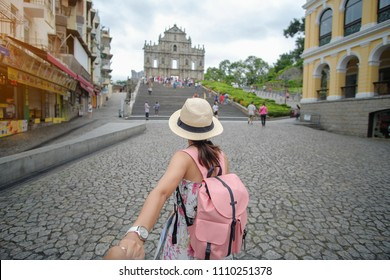 couple traveling backpacker with hat, Asian hipster traveler looking to Ruins of St. Paul's, Historic Centre of Macau, a UNESCO World Heritage Site. landmark and popular for tourist attractions